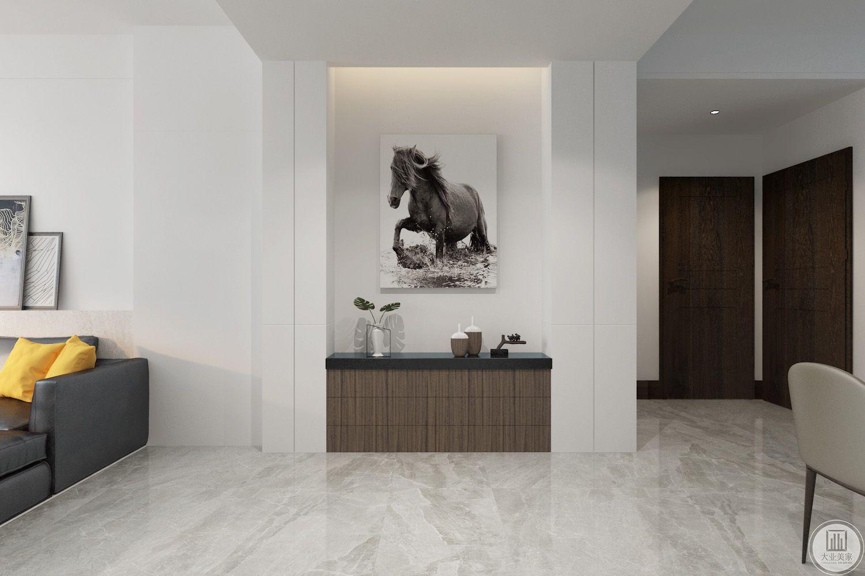 玄关装修效果图:玄关中间的墙面悬挂现代装饰画,下面采用实木装饰柜。