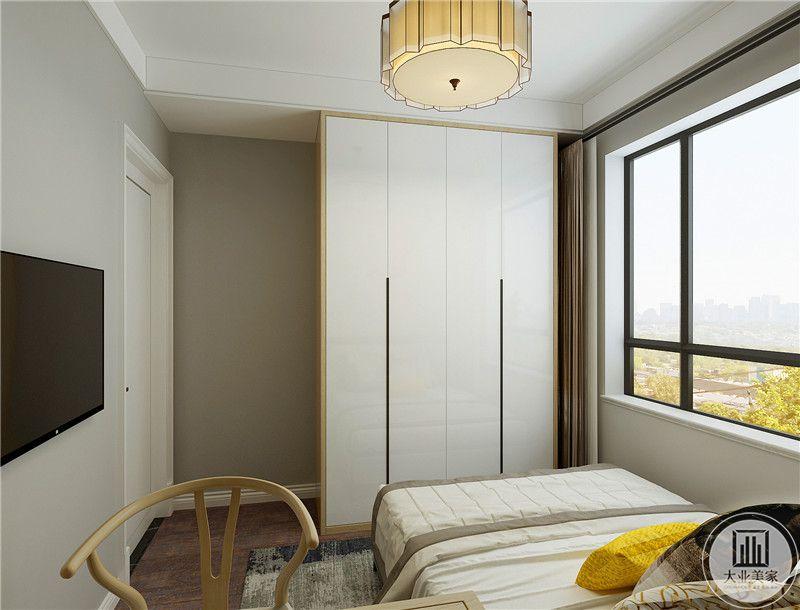 床尾放置大衣柜,墙面采用浅灰色壁纸,我是一侧的墙面悬挂电视。