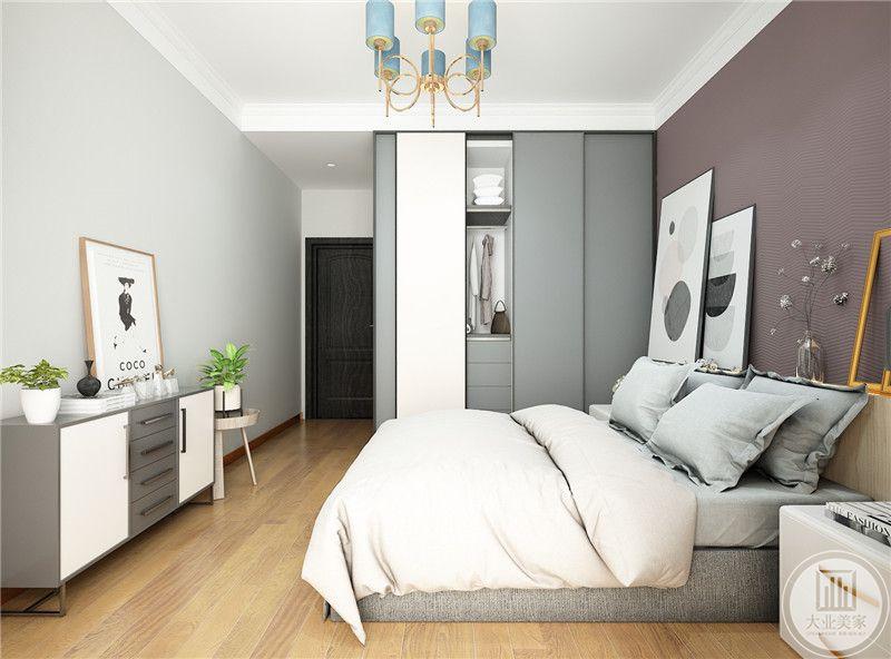 床尾墙面采用浅色壁纸,床尾放置小橱柜搭配现代装饰画。