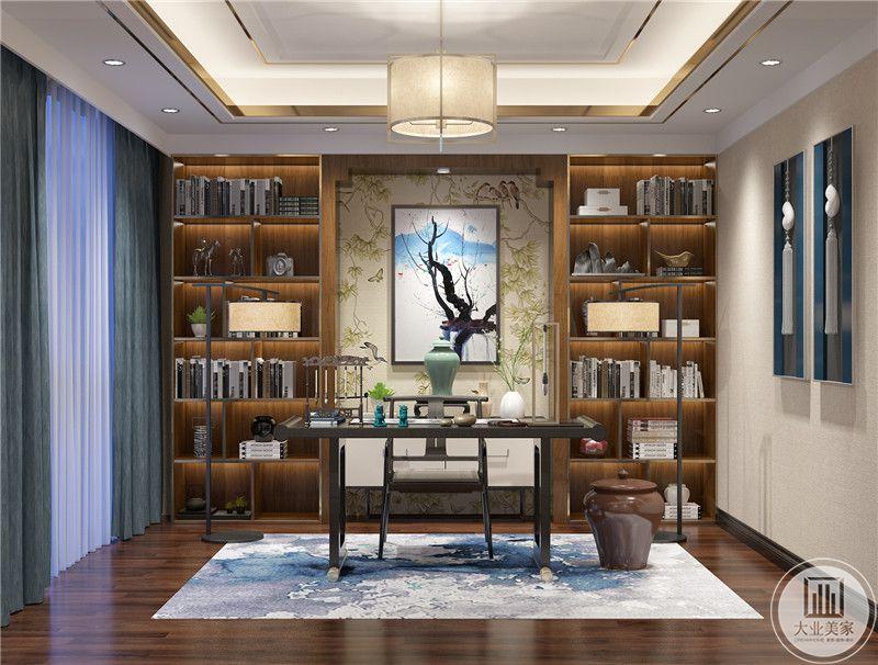 书房装修效果图:书房中心的墙上挂中式风景画,两侧用木质书柜,书桌上放置文房四宝。